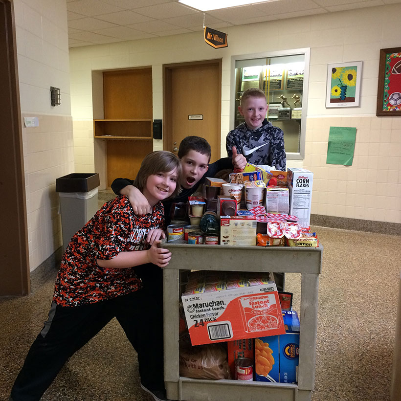 Students pushing cart of donations