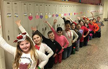 KC Club members pose with hearts they put up on lockers for Valentine's Day