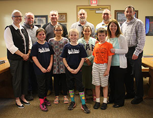 Members of the fourth grade Battle of the Books team pose for a photo with the Board of Education