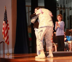 Maj. Jeffrey Oakes hugs his daughter Emily after surprising her at a school assembly