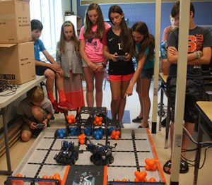 Students controlling and battling robots that they built and programmed