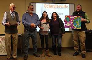 Emily Oakes poses with Lions Club representatives, art teacher Matt Roberts and her family at the Jan. 9 Board of Education meeting.