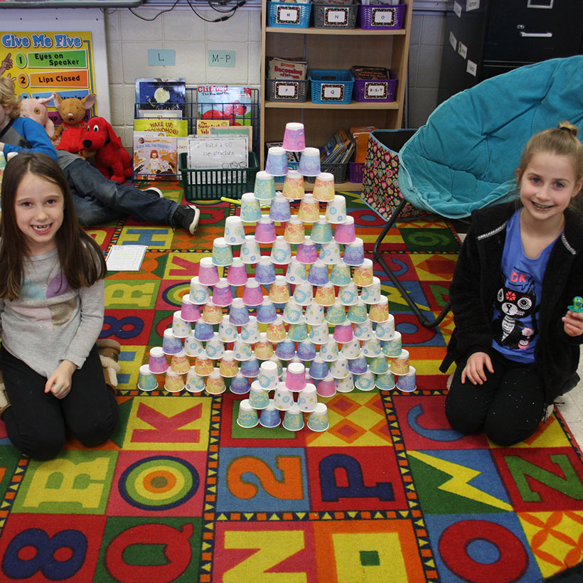 Students pose with 100 days tower they built