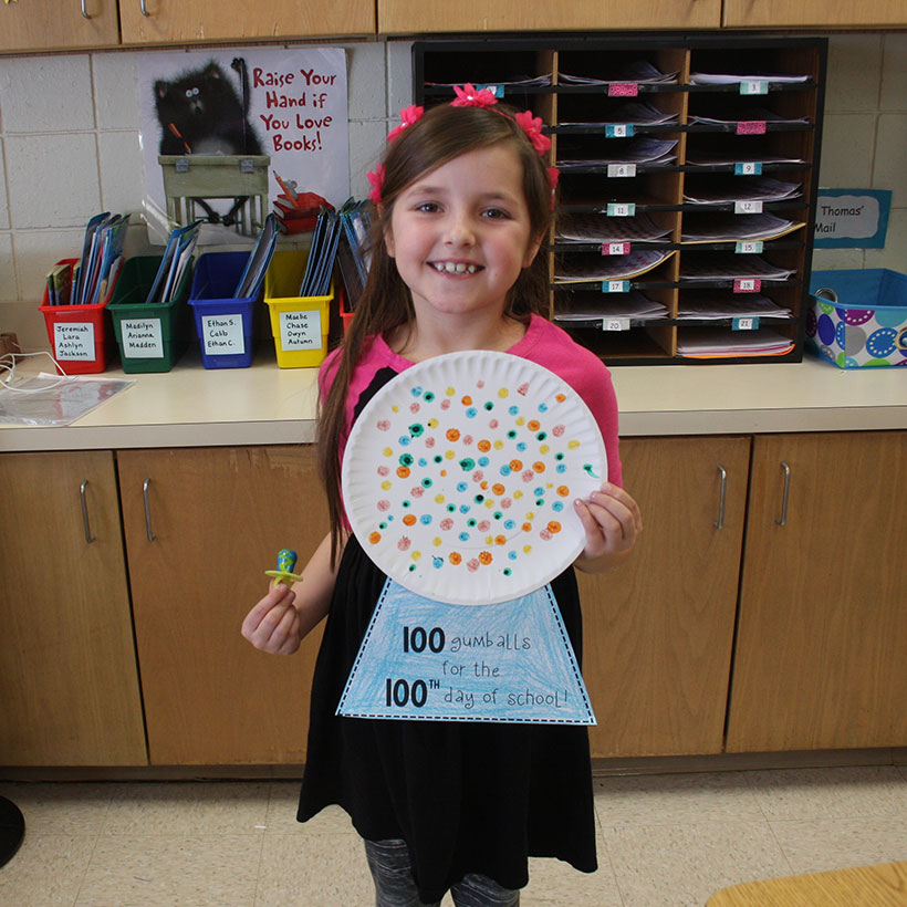 Student poses with 100 days gumball machine