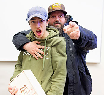 Junior George Olsen poses with designer Aaron Draplin after Draplin selected Olsen's sketchbook as his favorite
