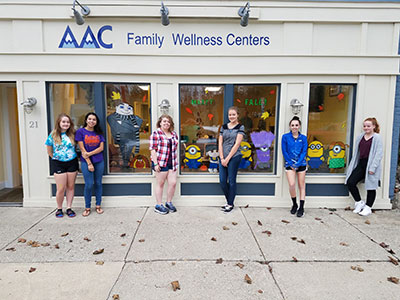 Students in Art Club pose for a photo with the mural they painted at AAC Chiropractic