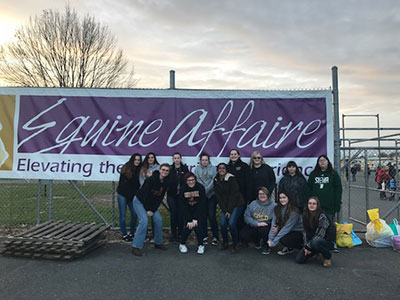 Students pose for photo in front of Equine Affaire sign