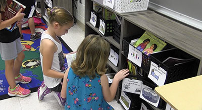 Students in Mrs. Reeves' second grade class select books to read from their new classroom library