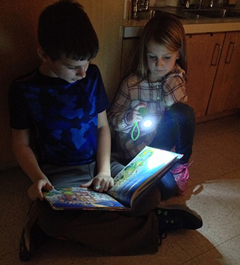 Students read by flashlight