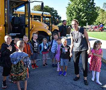Mrs. Beckett helps kindergarten students off the bus on their first day of school