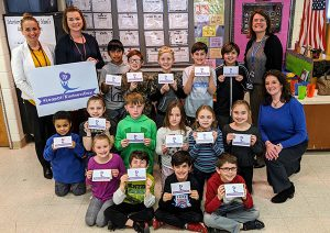 The photo depicts Rose Beckett, Elementary Principal, Stephanie Davis, 3rd Grade Teacher, Mrs. Davis' class, Cassandra Luthringer, School Counselor, and Sara Thornton, Schuylerville parent and member of the Saratoga County Chamber of Commerce.