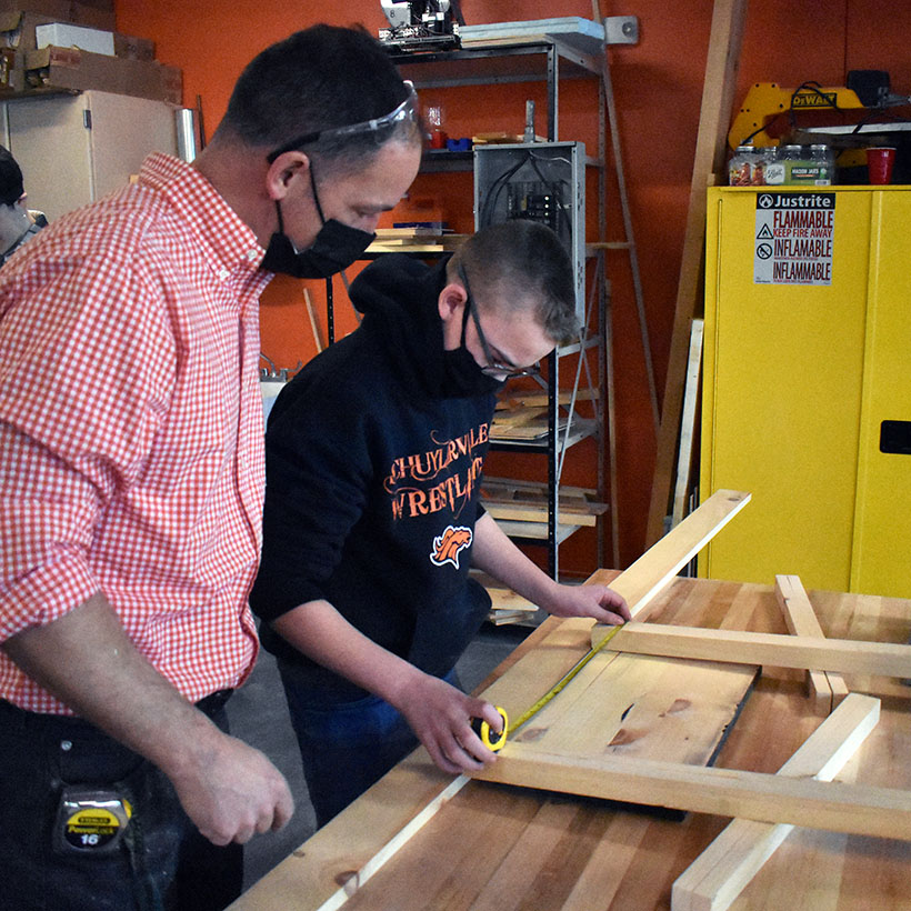 A construction trades student works with Mr. Gauci
